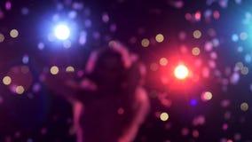 Из фокуса предпосылка с расплывчатым диско освещает девушку танцев акции видеоматериалы