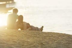 Из фокуса романтичные пары любовника отдыхают для захода солнца Стоковые Фотографии RF