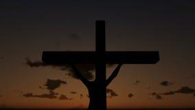 Иисус на кресте, конце вверх, заход солнца промежутка времени, день к ноче, отснятому видеоматериалу запаса
