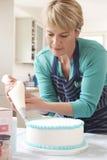 Именниный пирог замороженности женщины в кухне дома Стоковое фото RF