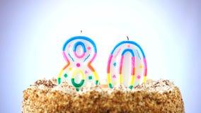Именниный пирог с горящей свечой дня рождения 80 Предпосылка изменяет цвет видеоматериал
