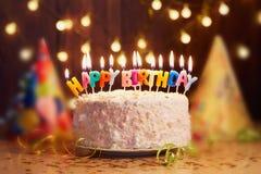 Именниный пирог с свечами, яркое bokeh светов Стоковые Изображения RF