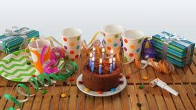 Именниный пирог шоколада с синью миражирует горение на деревенском деревянном столе с предпосылкой красочных лент, подарков Стоковые Изображения