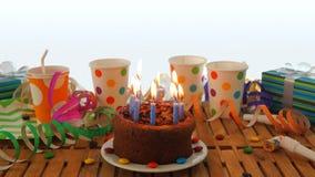 Именниный пирог шоколада с синью миражирует горение на деревенском деревянном столе с предпосылкой красочных лент, подарков Стоковая Фотография