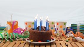 Именниный пирог шоколада с синью миражирует горение на деревенском деревянном столе с предпосылкой красочных лент, подарков Стоковое Изображение RF