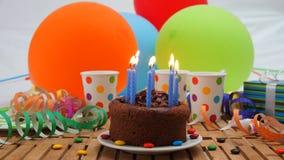 Именниный пирог шоколада с синью миражирует горение на деревенском деревянном столе с предпосылкой красочных воздушных шаров, под Стоковые Изображения