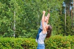 иметь потехи семьи счастливый outdoors Будьте матерью держать сына в воздухе как самолет Стоковая Фотография RF