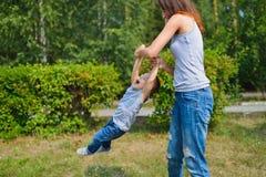 иметь потехи семьи счастливый outdoors Мать держа сына и закрутки как carousel взволнованности положительные Стоковые Изображения