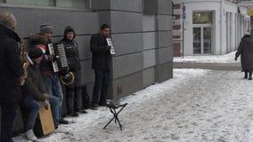 Имигрирующие люди играя аппаратуры музыки в бульваре города Падать снега вьюги видеоматериал