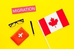 Иммиграция к концепции Канады Иммиграция текста около крышки пасспорта и канадского флага на желтом взгляд сверху предпосылки стоковое фото rf