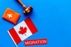 Иммиграция к концепции Канады Иммиграция текста около крышки пасспорта и канадского флага, молотка на голубой верхней части предп стоковое фото