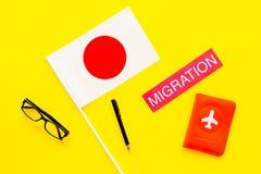 Иммиграция к концепции Японии Иммиграция текста около крышки пасспорта и японцы сигнализируют на желтом взгляд сверху предпосылки стоковое изображение rf