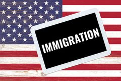 Иммиграция, текст на ПК таблетки над нами флаг стоковое изображение rf