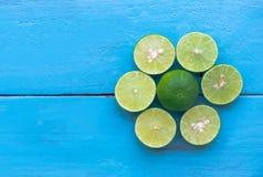 лимон известки неполная вырубка на голубой деревянной предпосылке водительство Стоковая Фотография