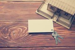 имущество принципиальной схемы реальное Модельный дом, ключи, пустая визитная карточка на деревянном столе Взгляд сверху тонизиро Стоковое Фото