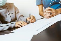 Имя более старых женщин подписывая внутри полис страхования жизни Стоковые Изображения RF