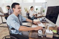 Инвалид в кресло-коляске работает в офисе на компьютере Стоковые Изображения RF