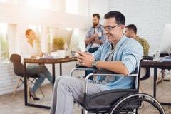 Инвалид в кресло-коляске работает в офисе Он говорит на smartphone Стоковые Фото