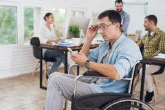 Инвалид в кресло-коляске работает в офисе Он говорит на smartphone Стоковая Фотография RF