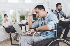 Инвалид в кресло-коляске работает в офисе Он сидит заботливо Стоковая Фотография