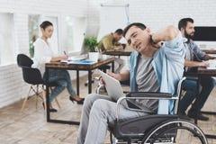 Инвалид в кресло-коляске работает в офисе Он чувствует desease Стоковая Фотография RF