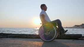Инвалид сидя в кресло-коляске на обваловке, жизнерадостный с ограниченными возможностями человек на инвалидном экипаже, поврежден сток-видео