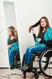 Инвалидная девушка на кресло-коляске расчесывая волосы Стоковые Фотографии RF