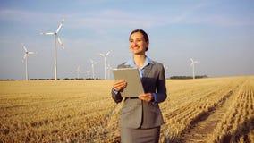 Инвестор в ветротурбинах с компьютером оценивая ее вклад на месте видеоматериал