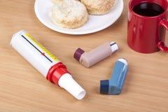 2 ингалятора астмы и измеритель прокачки взгляда украдкой на таблице Стоковая Фотография