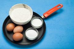 Ингредиенты блинчиков - яйца, мука, молоко, сахар в утварях кухни в сковороде стоковые фотографии rf