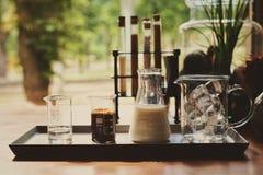 Ингредиенты для делать холодный latte кофе, молоко эспрессо кубов льда и сладкий сироп служили в различных пробирках на деревянно стоковое фото rf