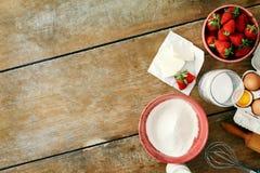 Ингридиенты деревенского стиля установленные сырцовые варя торт пирога клубники сватают стоковая фотография