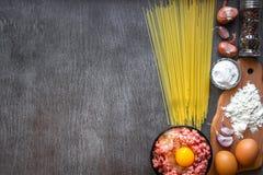 Ингридиенты для варить макаронные изделия Спагетти, яичка, оливковое масло, чеснок, minsed мясо, перец и свежий сельдерей на дере Стоковые Изображения RF