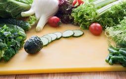 Ингридиенты для варить салат зеленеют, овощи на желтой доске стоковые фото