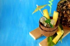 Ингридиенты для коктеиля colada pina Кубы льда и части ананаса служили в половине кокоса украшенные с зонтиком Стоковые Изображения