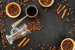 Ингридиенты для кофе Зажаренные в духовке кофейные зерна и циннамон на черном copyspace взгляд сверху предпосылки Стоковые Изображения RF