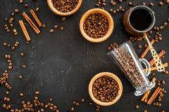 Ингридиенты для кофе Зажаренные в духовке кофейные зерна и циннамон на черном copyspace взгляд сверху предпосылки Стоковые Изображения