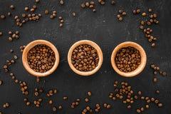 Ингридиенты для кофе Зажаренные в духовке кофейные зерна и циннамон на черном взгляд сверху предпосылки Стоковые Фото