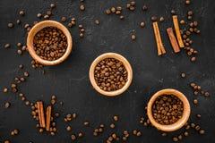 Ингридиенты для кофе Зажаренные в духовке кофейные зерна и циннамон на черном взгляд сверху предпосылки Стоковые Фотографии RF