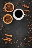 Ингридиенты для кофе Зажаренные в духовке кофейные зерна и циннамон на черном copyspace взгляд сверху предпосылки Стоковое Фото