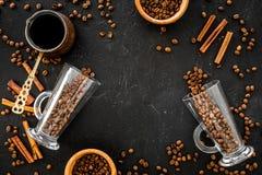 Ингридиенты для кофе Зажаренные в духовке кофейные зерна и циннамон на черном copyspace взгляд сверху предпосылки Стоковая Фотография