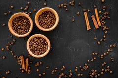 Ингридиенты для кофе Зажаренные в духовке кофейные зерна и циннамон на черном copyspace взгляд сверху предпосылки Стоковое Изображение