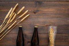 Ингридиенты для пива Пивоваренный ячмень около пивной бутылки и стекла на деревянном copyspace взгляд сверху предпосылки Стоковая Фотография RF