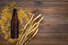 Ингридиенты для пива Пивоваренный ячмень около пивной бутылки и стекла на деревянном copyspace взгляд сверху предпосылки Стоковые Фото