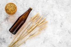 Ингридиенты для пива Пивоваренный ячмень около стекел и бутылки пива на сером copyspace взгляд сверху предпосылки Стоковое Изображение RF