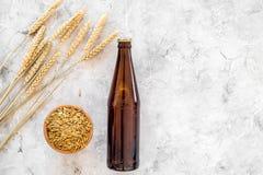 Ингридиенты для пива Пивоваренный ячмень около стекел и бутылки пива на сером copyspace взгляд сверху предпосылки Стоковые Фото