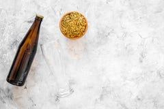 Ингридиенты для пива Пивоваренный ячмень около стекел и бутылки пива на сером copyspace взгляд сверху предпосылки Стоковые Изображения