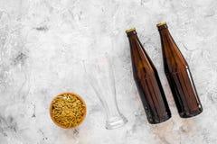 Ингридиенты для пива Пивоваренный ячмень около стекел и бутылки пива на сером copyspace взгляд сверху предпосылки Стоковая Фотография RF