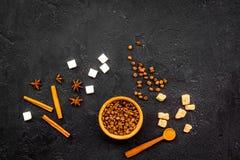 Ингридиенты для сладостной хлебопекарни Циннамон, какао, сахар, кофе на черном космосе экземпляра взгляда столешницы Стоковое Изображение