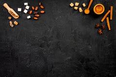 Ингридиенты для сладостной хлебопекарни Циннамон, какао, сахар, на черном космосе экземпляра взгляда столешницы Стоковое Фото